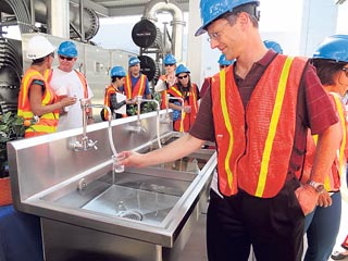 An engineer prepares to taste water from the reverse-osmosis pilot treatment system at an Orange County Water District plant.